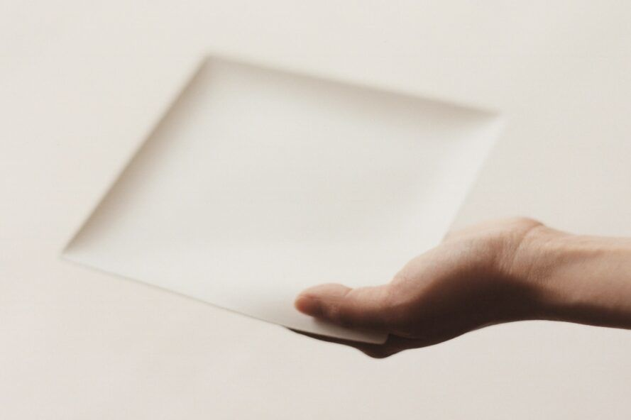A hand holding a square plate.