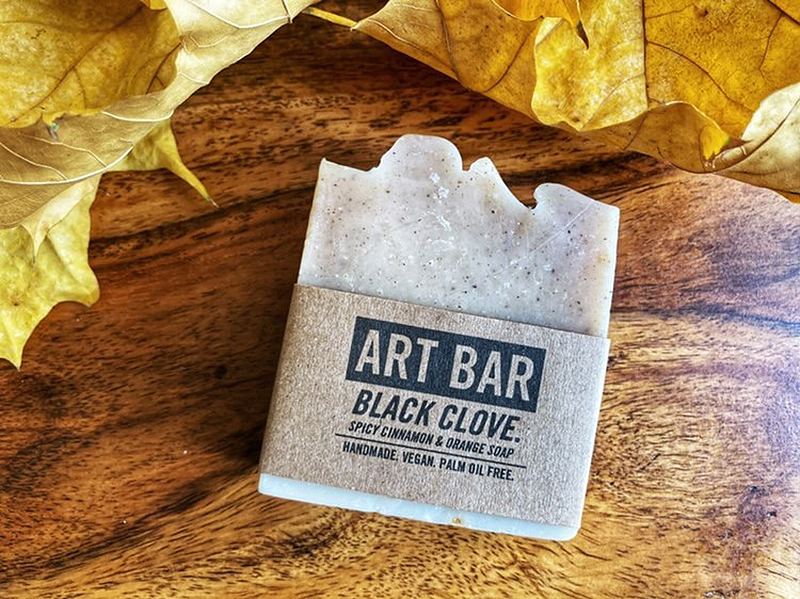 """beige soap with label that reads, """"Art Bar, Black Clove,"""" near some yellow leaves"""