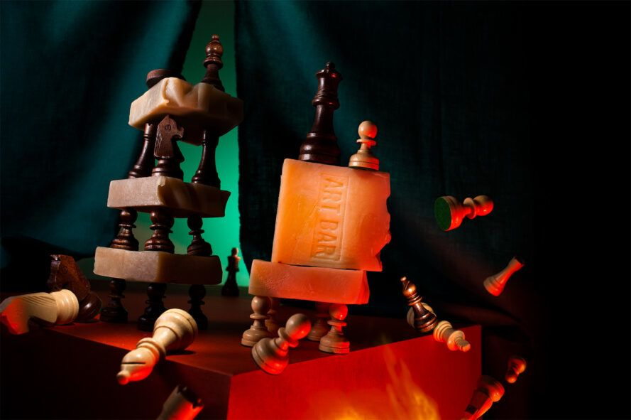 artistic composition of natural soaps and chess pieces