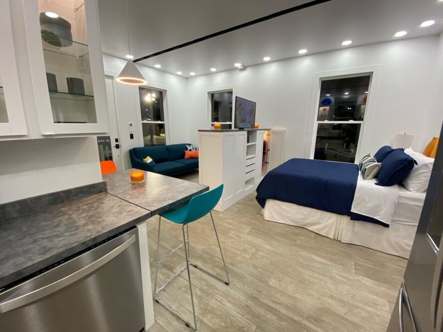 gray tiny home interior with blue bed and blue sofa