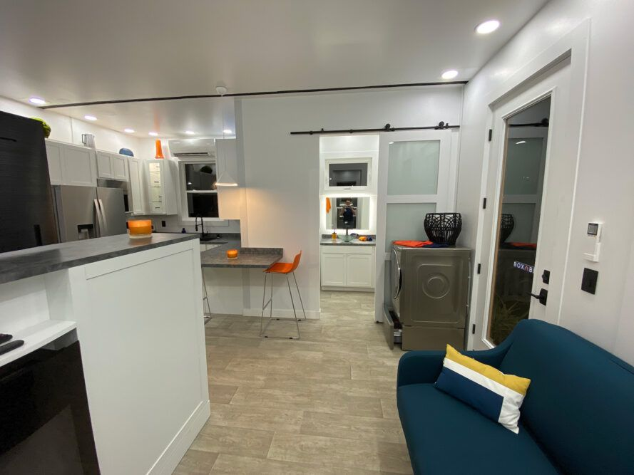 tiny home interior with washer on one side of front door and couch on opposite side