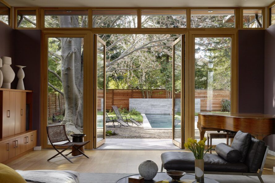 A living room with a dark gray chaise lounger that looks out onto open floor-to-ceiling glass doors that show the backyard.