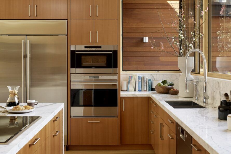 A kitchen with wood cabinets, white marble counters and stainless steel appliances built in to the cabinets.