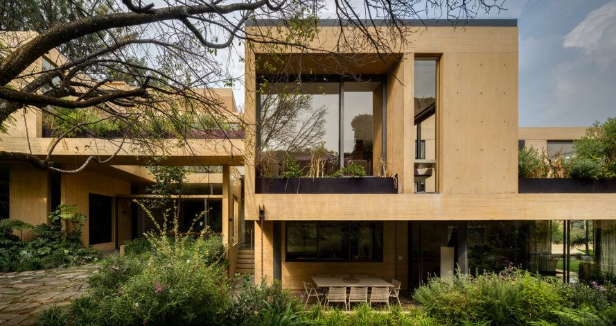 Tan house with huge windows and green roof