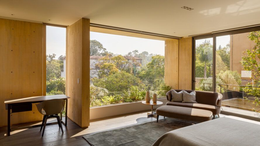 A glass wall facing the bed with a view of the forest