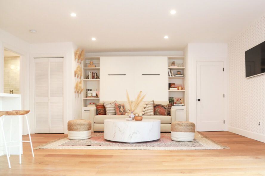 Bright living room, white walls and light wood floors. There is a cream-colored sofa in front of the two bookshelves.
