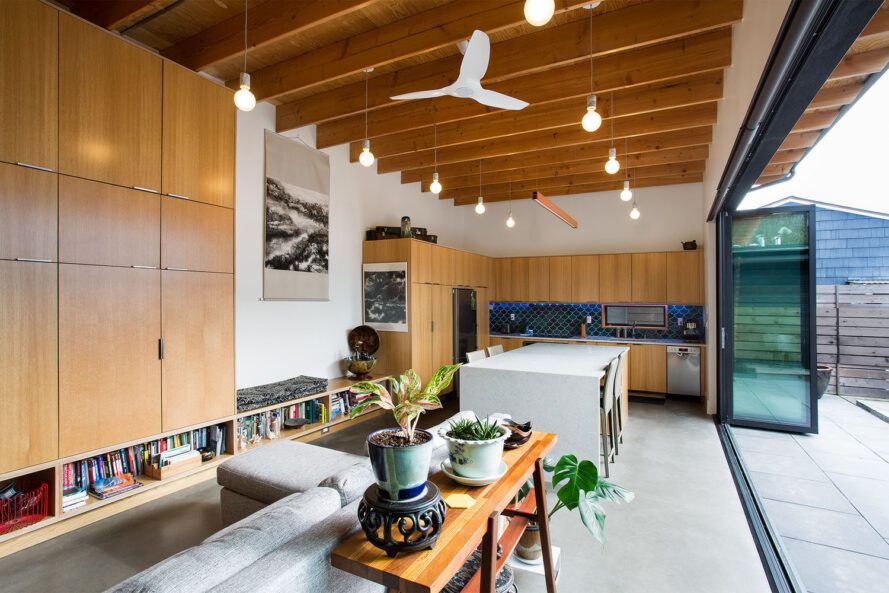 Natural mid-tone wood decorates the room through cabinets and exposed wood beam ceilings above the living room and kitchen.