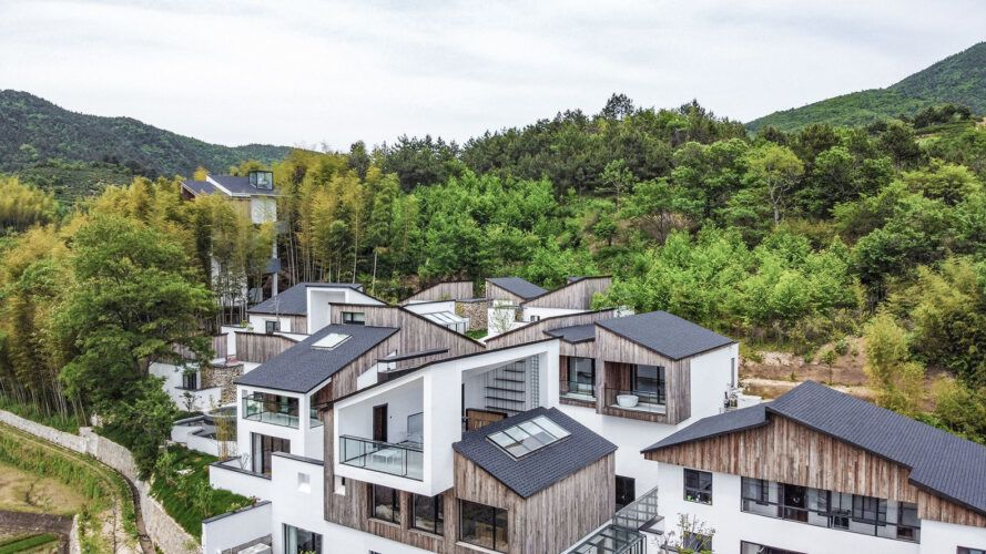 aerial view of wood and white homes in a forest
