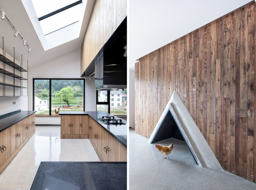 On the left is the kitchen with wooden cabinets and black counters.On the right is a wooden decorative wall with a triangular fireplace at the bottom