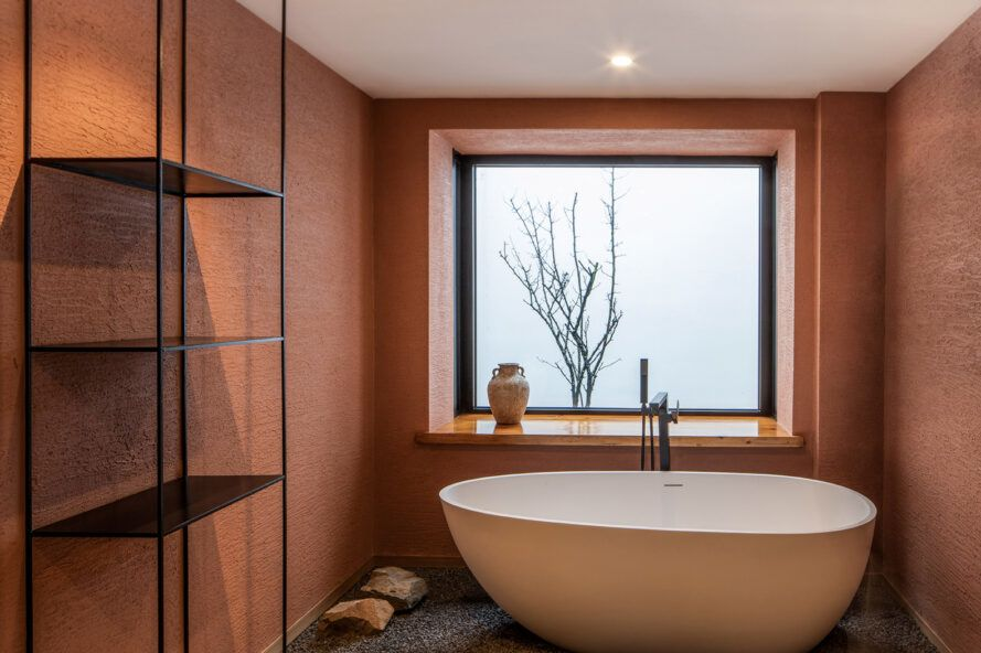 Bathtub in front of large windows