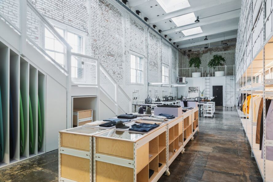 White walls lining a clothing facility with wood workbenches.