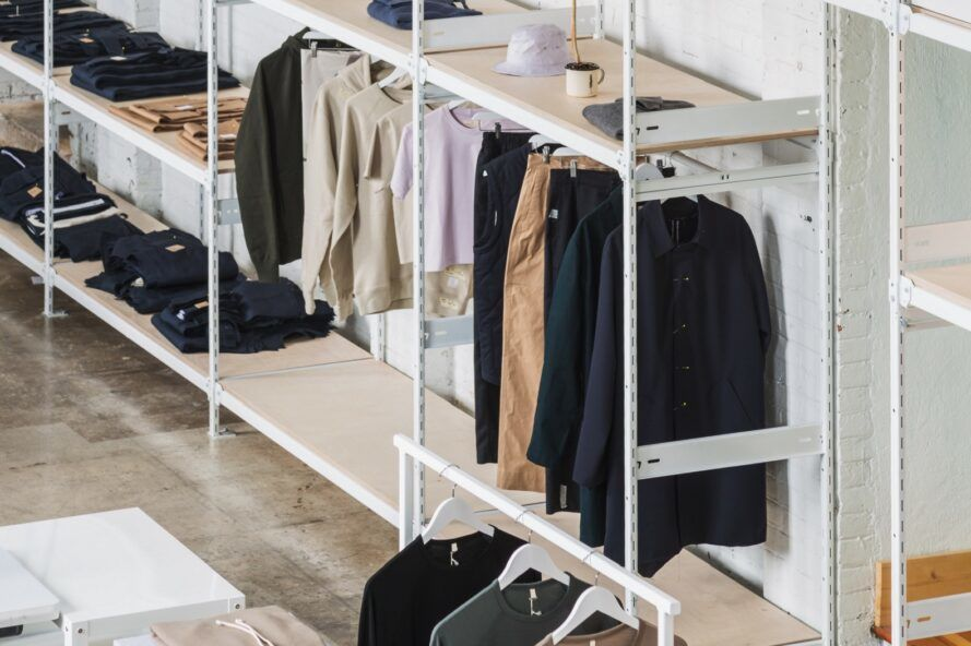 White racks of neutral-toned clothes.