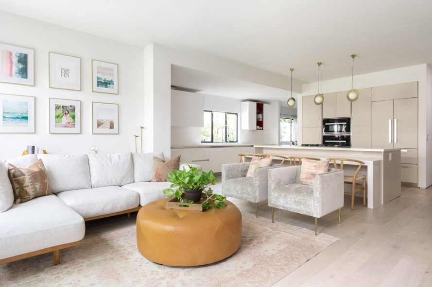 The bright living room is furnished with a white sofa, two white chairs and a mustard yellow coffee table pouf.