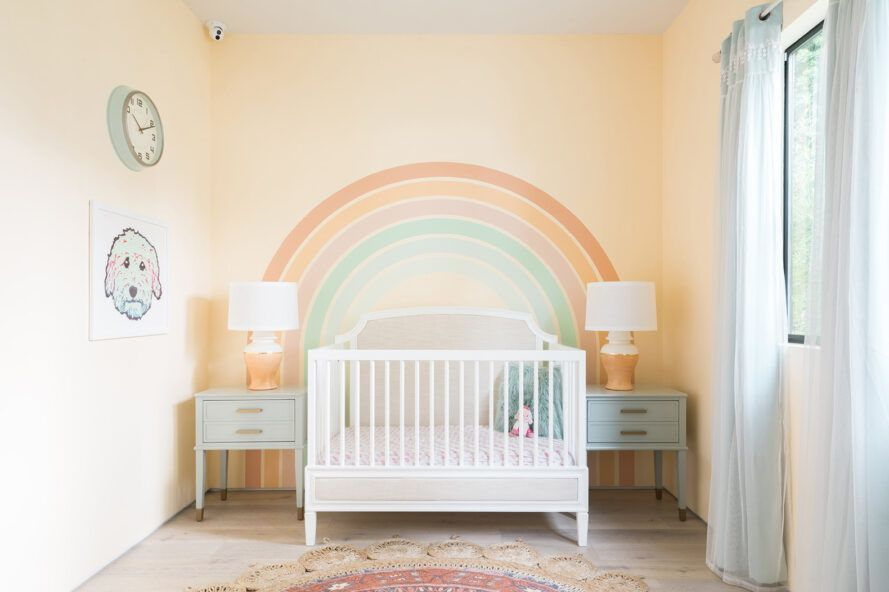 A nursery with a white crib, two cribs, two lamps and a yellow wall with a rainbow painted on the wall.