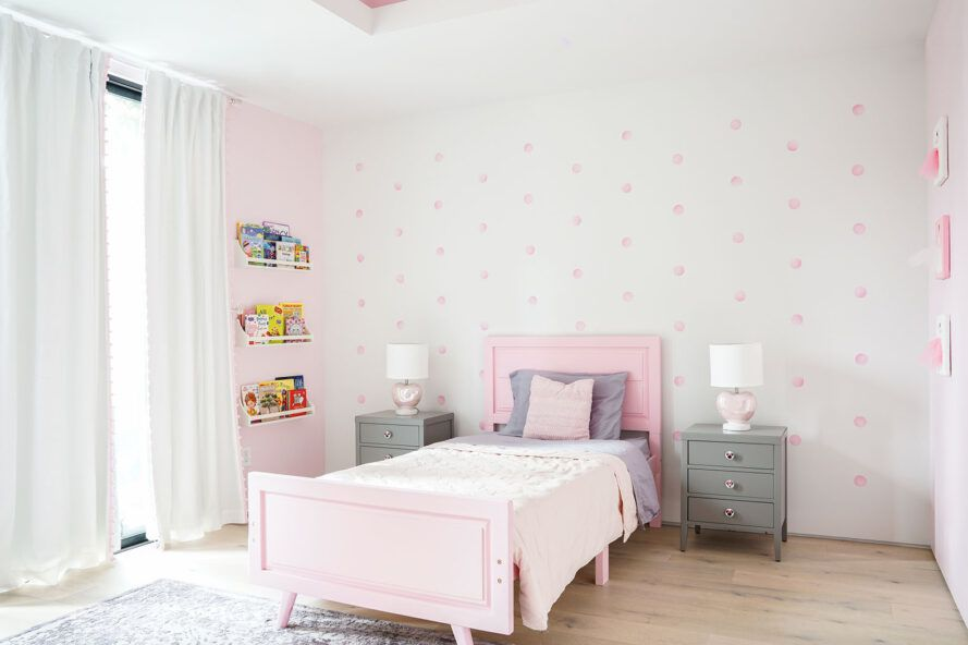 The children's room has white and pink walls and a pink bed.