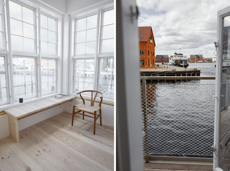 The chairs near the window of the houseboat have a view of the harbor