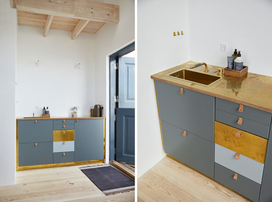 Hotel kitchenette with small sink and gray cabinets
