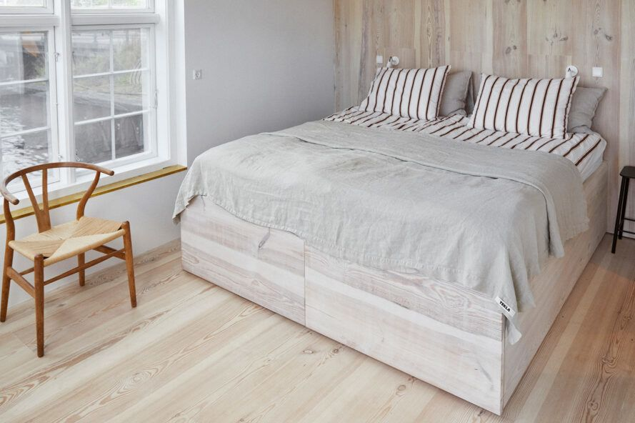 There is a fluffy white bed in the bright white room with a wood grain wall on the wall