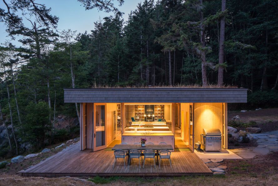 Wooden houses with grass roofs are lit from the inside at night