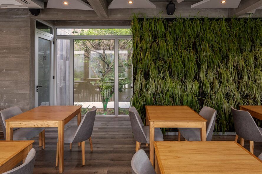 An interior dining area with wood tables and chairs, with a green wall in the background.