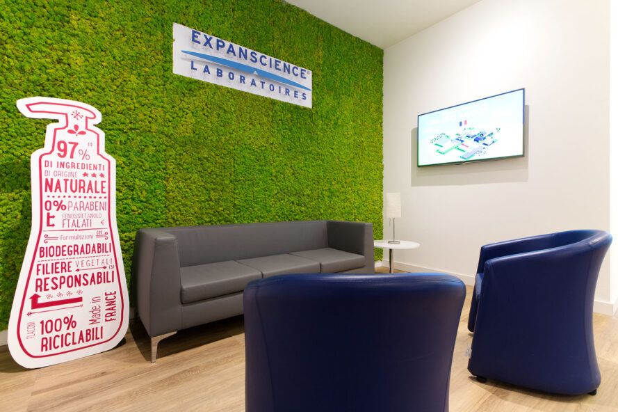 sofa and blue chairs in front of moss wall