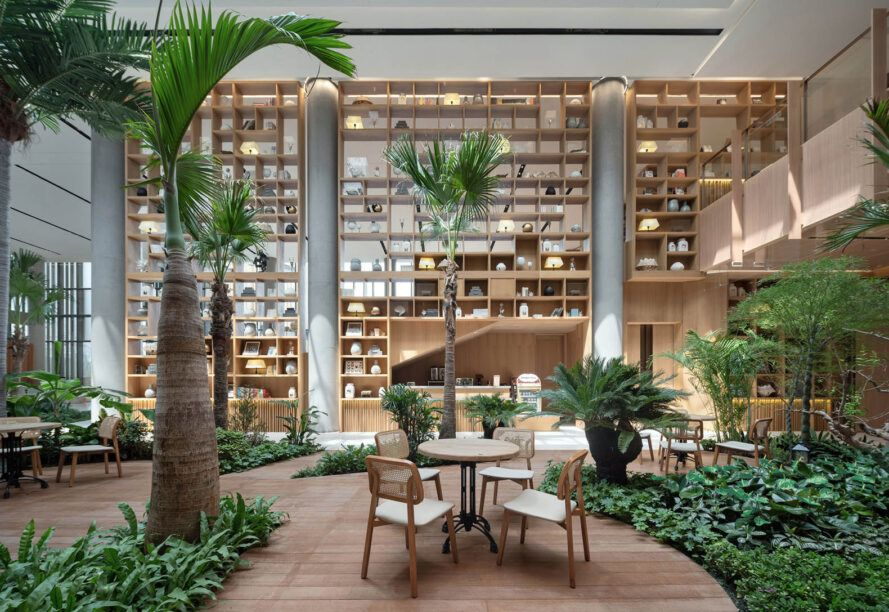 The dining table in the middle of the indoor rainforest area has large built-in wooden shelves on parallel walls.