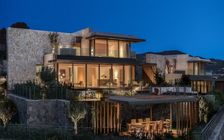 villa with glass walls lit from within at dusk
