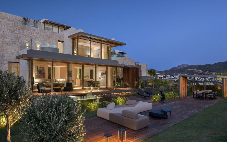 gray and white patio furniture next to villa with glass walls