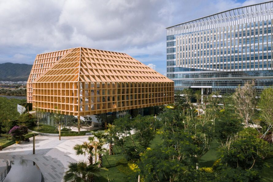 large building with wood grid roof next to glass building