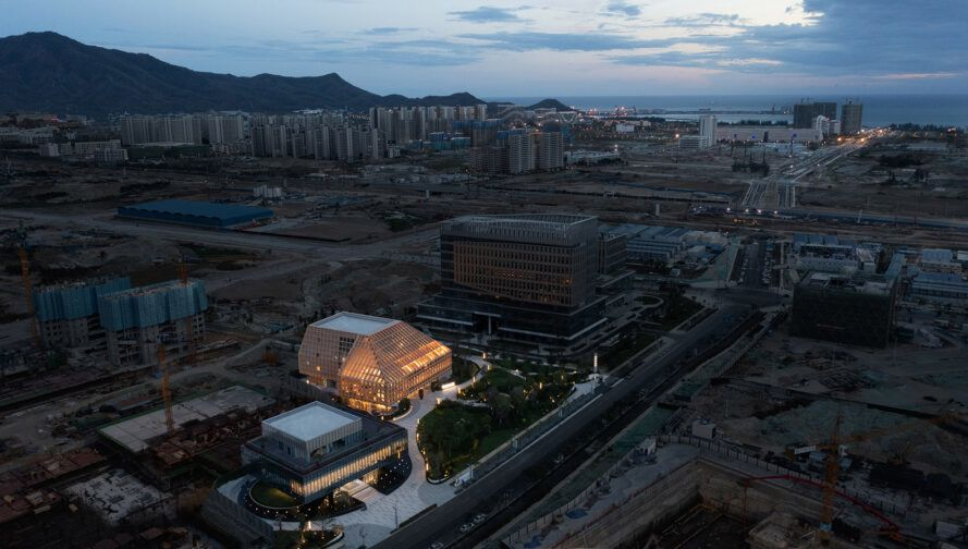 aerial view of glass and wood building in a city under development