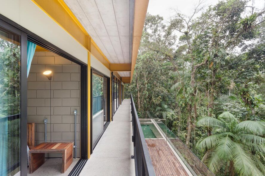 The bedroom with glass walls leads to a narrow balcony