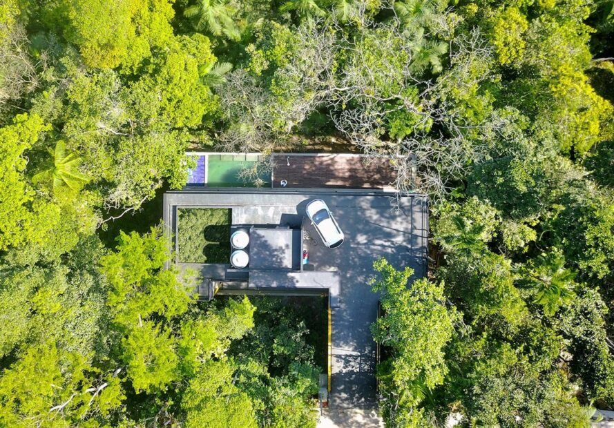 Aerial view of a small three-story house in the forest