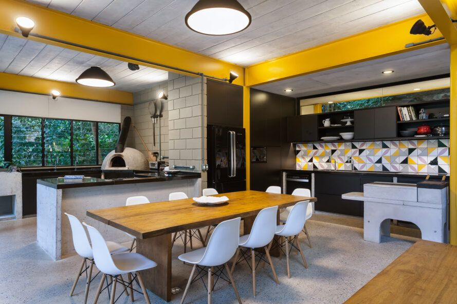 Wooden dining table with white chairs near the black, white and yellow kitchen