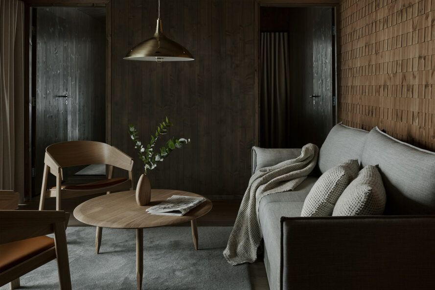 Dark living room with beige sofa and wooden round coffee table