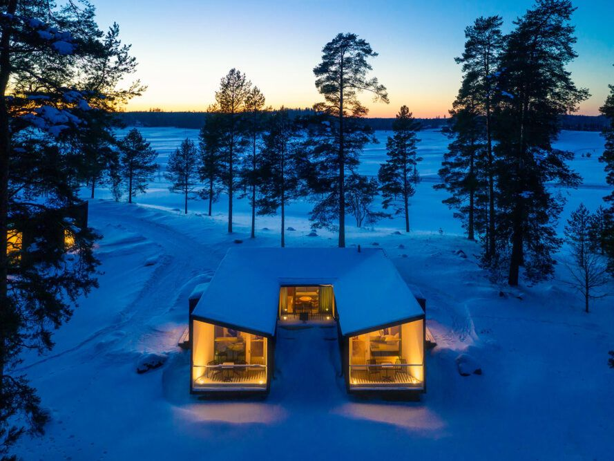 Snow-covered U-shaped hut lit from the inside at dusk