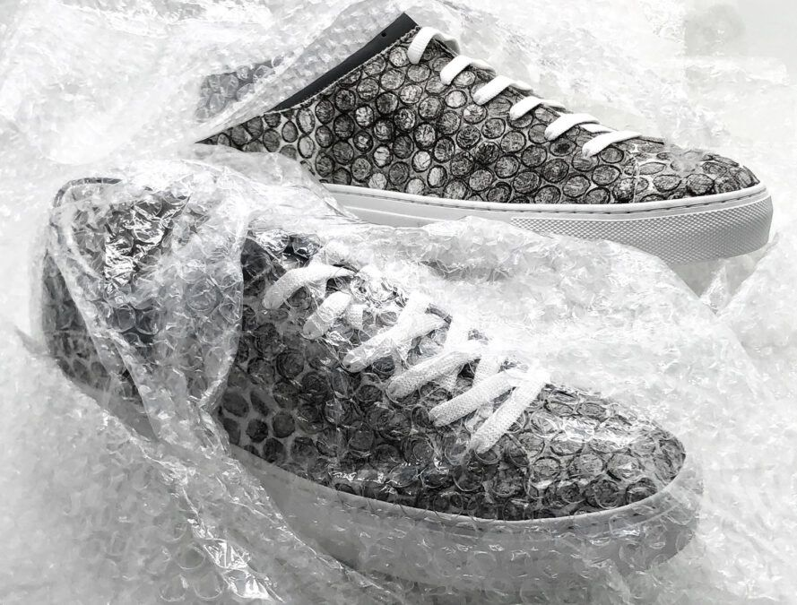 Two grey sneakers with bubble wrap pattern on the canvas and bubble wrap around