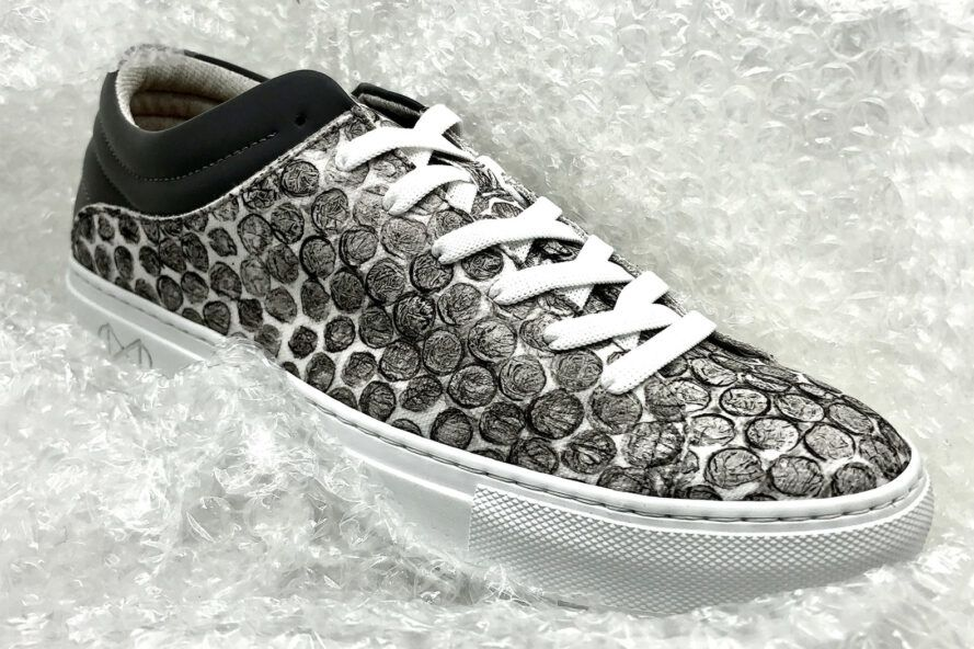 Grey and white vegetarian shoes with bubble wrap printed on the canvas, surrounded by bubble wrap