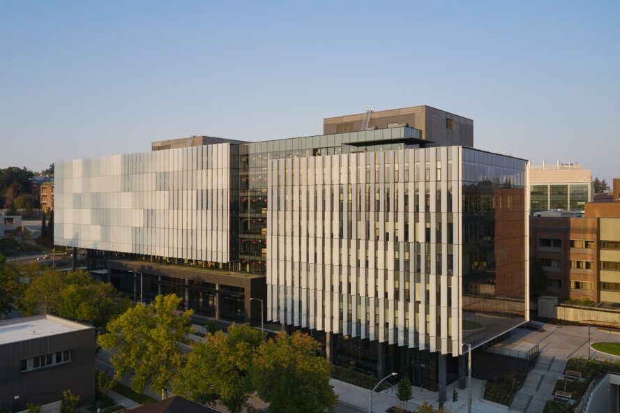 Two rectangular volumes creating one large education center with a silver facade on a campus.