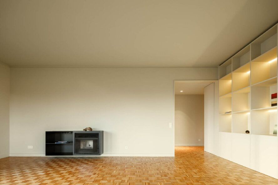 A room with wooden floors and white walls. Inside one wall is a dark gray cabinet and a white cabinet on the right.
