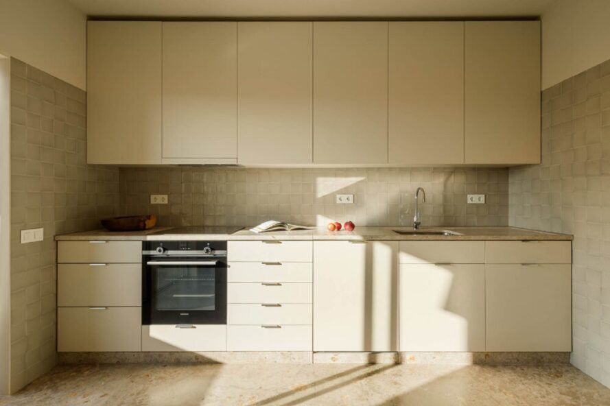 The kitchen has an off-white floor and a tile backsplash. The kitchen has white cabinets and a black oven.