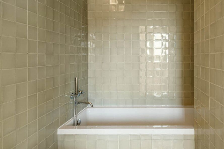 The bathroom with bathtub is surrounded by gray square tiles.