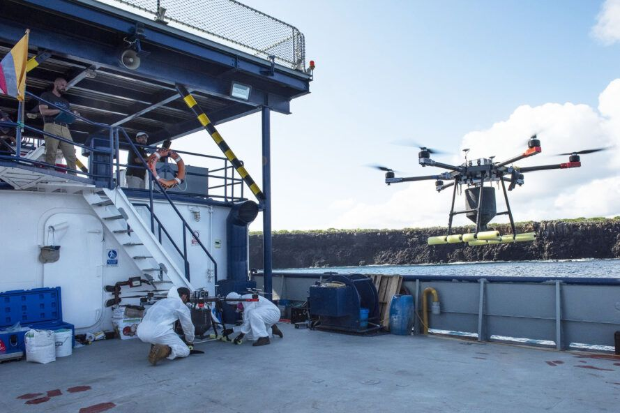 A drone rises from the deck of a ship.