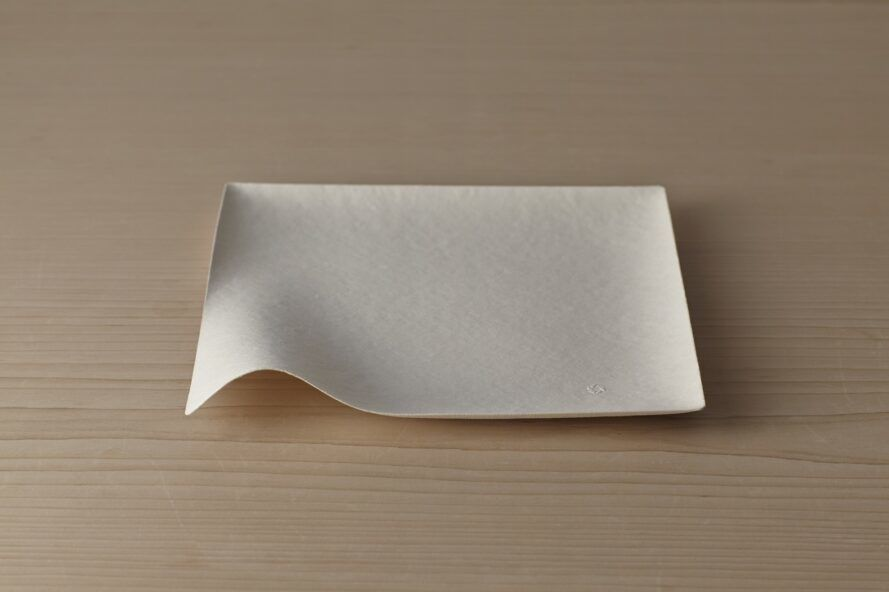 A square plate with a curved lip on the front left corner.