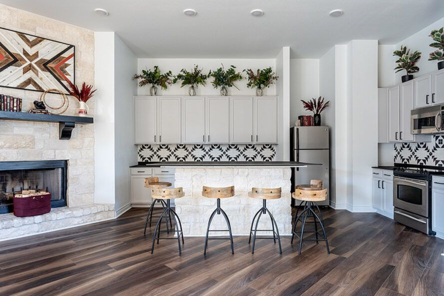 The kitchen has white cabinets and walls and dark wood floors. There is a small island surrounded by six wooden benches, with a fireplace on the left and a refrigerator, stove, oven and microwave on the right.