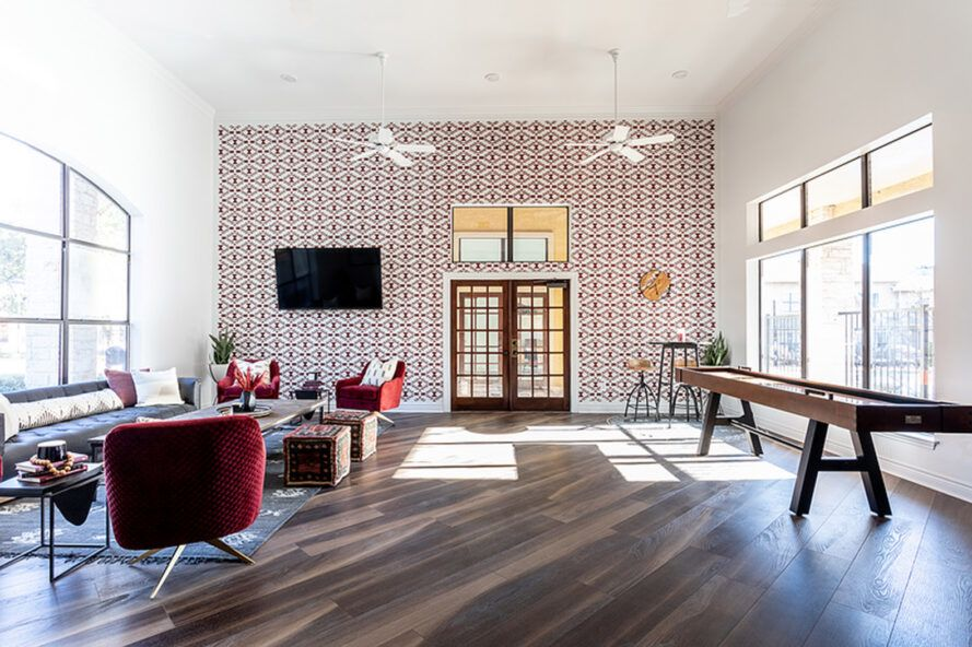 A living room space, with white and brick red patterned wallpaper pasted on a key wall, surrounded by two white walls, with large windows on the left and right. The rooms feature wooden floors, red furniture and wooden tables.