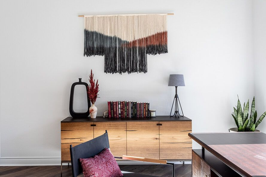 An office space with a drawer against the wall, and a cream, blue and red textile artwork hanging on the wall.