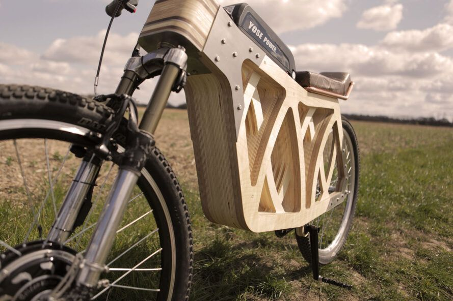 The undercarriage of a wooden e-bike on a grassy lawn.