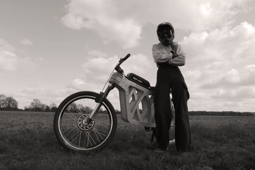 A black-and-white photo of a person in a bike helmet standing next to a wooden e-bike.
