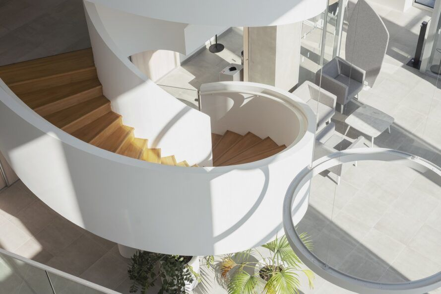 A white and wood spiral staircase leading down to the building's main level.