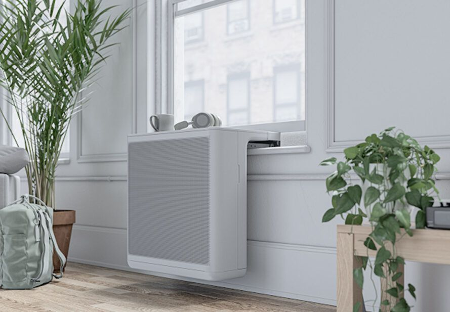 The interior of a white minimalist apartment with an AC unit attached to the window.